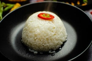 Jasmine Sticky Rice served in a black bowl with red chilli on top