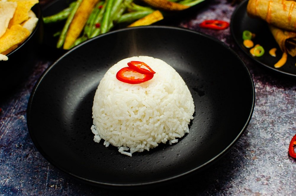 Jasmine Sticky Rice served in a black bowl with sliced red chilli on top