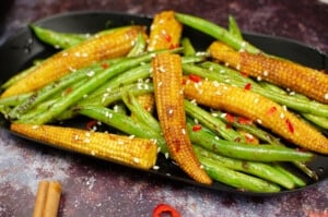 Stir-Fried Vegetable Side Dish served in a black dish with chopped chillies and sesame seeds on top