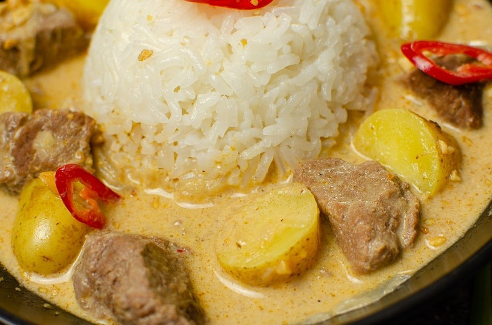 Thai beef massaman curry in a bowl wwith sticky rice in the middle with red chillies on top