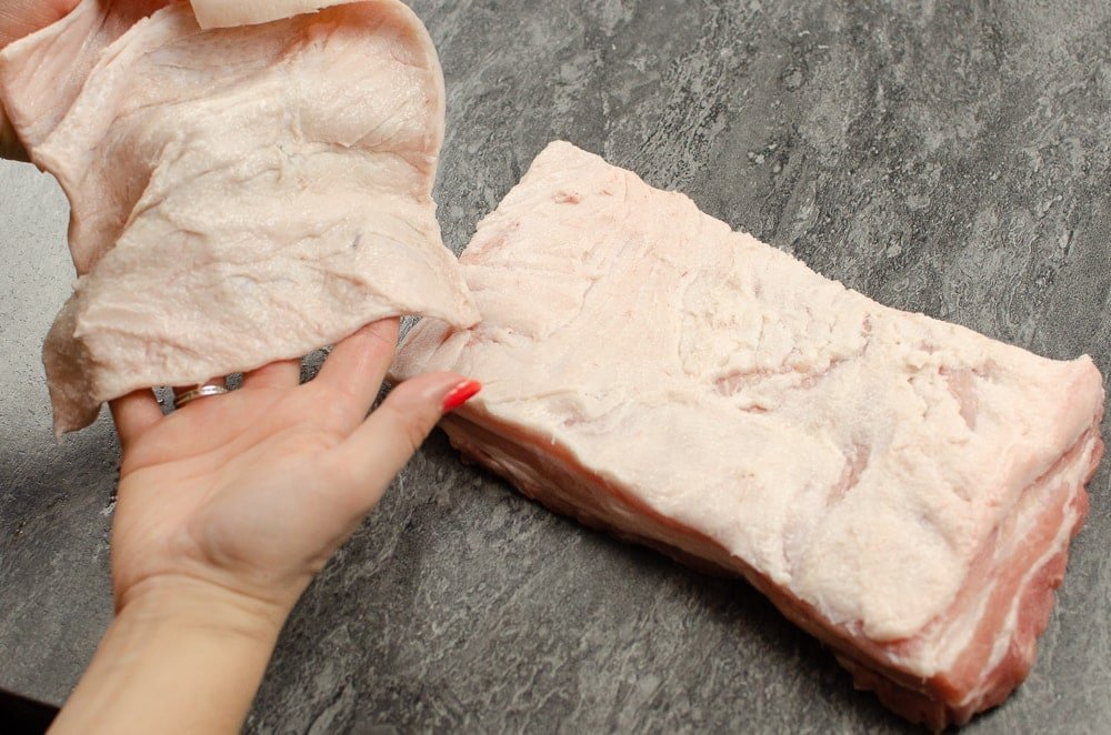 Kay holding the pork belly skin in her hands which she has taken off