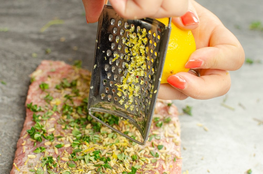 Grating lemon zest onto our pork belly