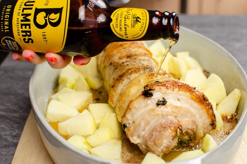 Pouring Bulmers Apple Cider over our pork belly and apple chunks in a green casserole dish