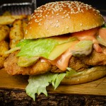 Spicy Chicken Burger on a wooden board served with chips behind the burger