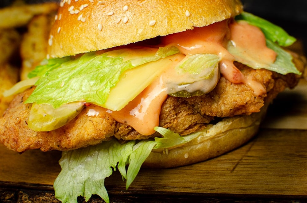 Spicy chicken burger with bang bang sauce served on a wooden board