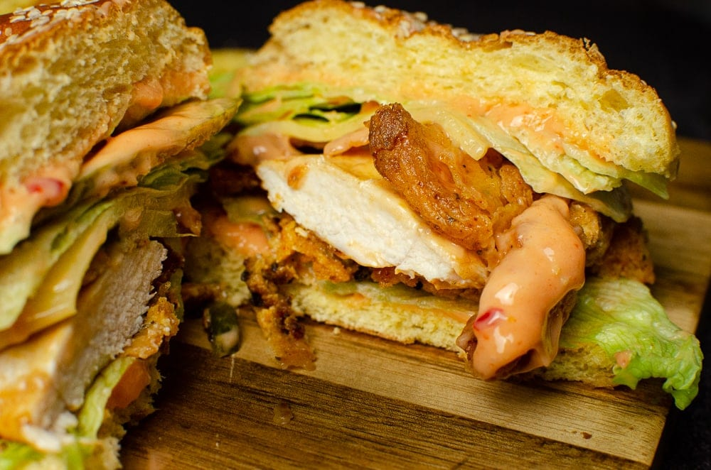 Spicy Chicken Burger been cut in half on a wooden board