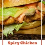 Pinterest image of our Spicy Chicken Burger served on a wooden board with sauce dripping out from the bun
