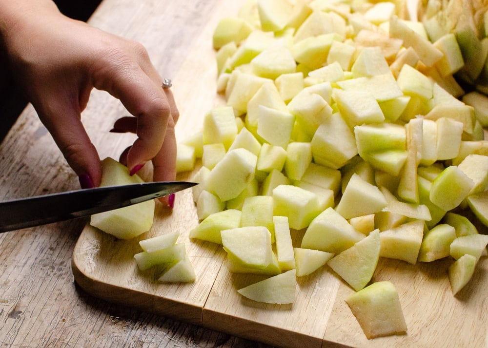 Chopping up cooking apple on a wooden chopping board