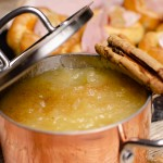 Homemade Apple Sauce in a copper pot with a cinnamon stick on top with Yorkshire puddings in the background