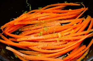 Grated carrot with lime zest on top in a black bowl