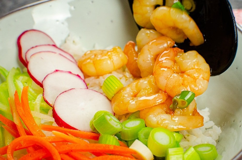Honey and garlic Prawn poke bowl prawns poured on to jasmine rice with grated carrot,cucumber,radishes and spring onion.