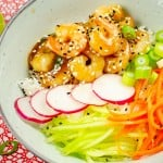 Honey and Garlic prawn poke bowl served with grated carrot,cucumber ,radishes and spring onion in a green bowl