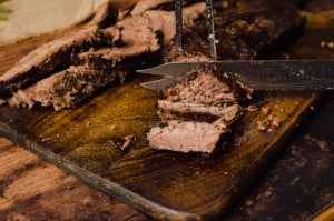 Cutting the beef brisket joint with a silver knife on a dark wooden board
