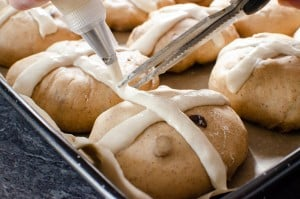 Piping the cross onto the Hot Cross Buns with the flour mix and cutting it with scissors