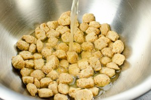 Textured vegetable protein soaking in vegetable stock in a silver bowl