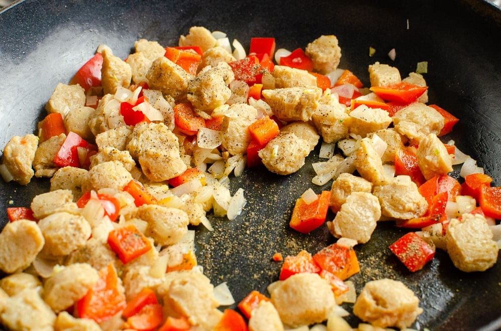 Textured vegetable protein,chopped onions and chopped red peppers cooking in a cast iron pan