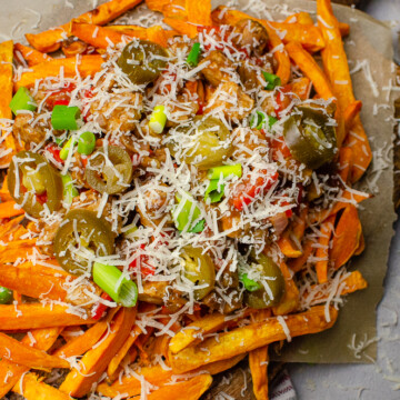 Loaded Vegan Sweet Potato Fries on a dark wooden board with grated Parmesan cheese on top
