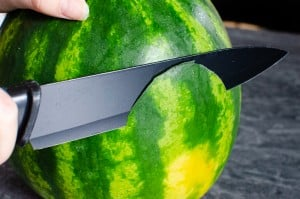 Cutting a slice out of the watermelon to make a flat surface for the melon to give it a flat bottom