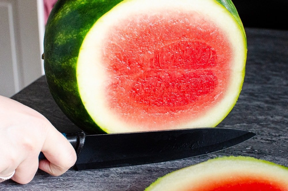 Cutting the top of the watermelon with a black knife