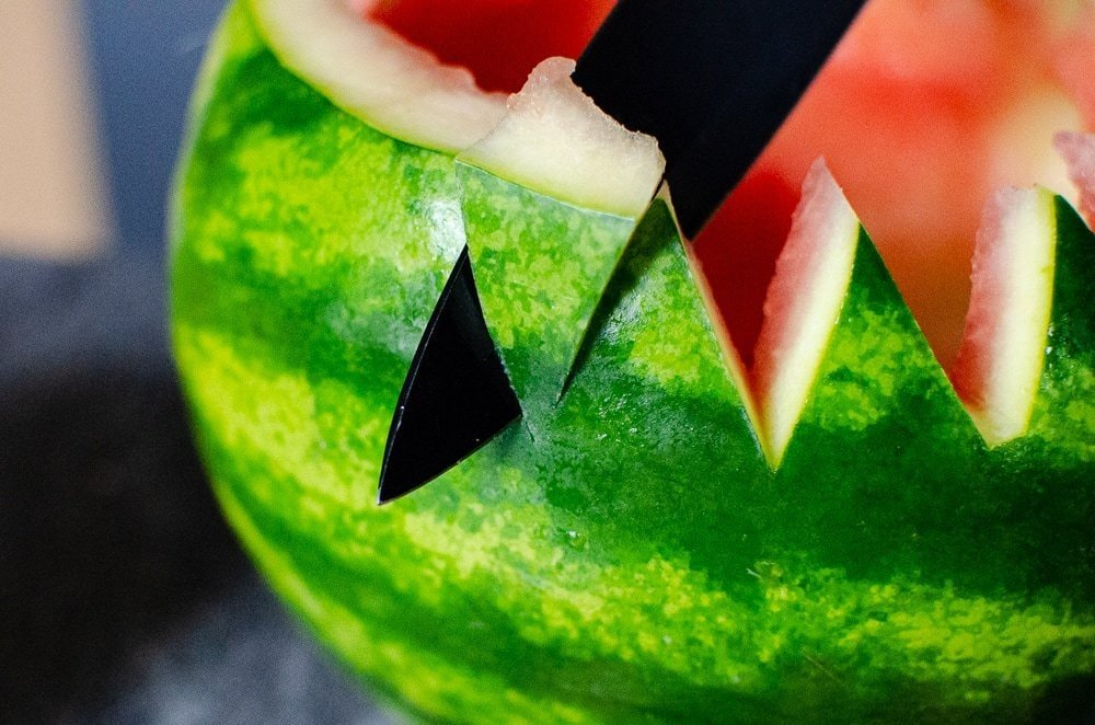 Cutting triangle shapes around the edge of the watermelon to make a bowl