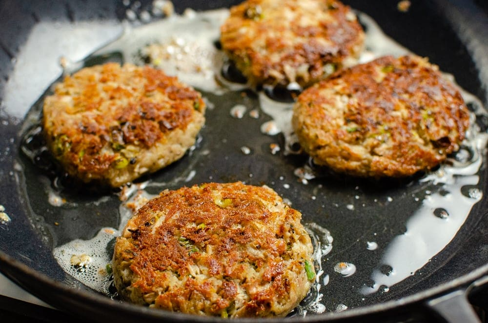 Frying the Easy Tinned Tuna Burgers in a black cast iron pan