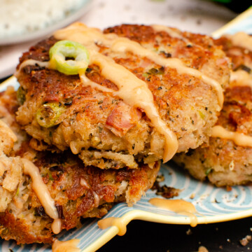 Easy Tinned Tuna Burgers on a blue,white and yellow dish served with spring onion and drizzled spicy mayo sauce on top