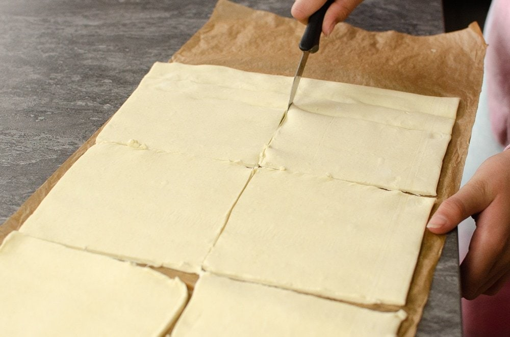 Cutting puff pasty into squares to make the turnovers