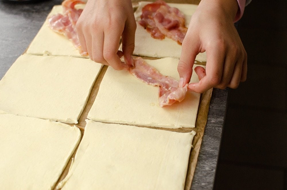 Placing bacon strips onto puff pastry squares