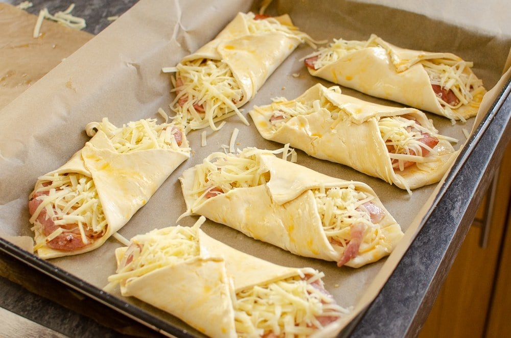 Flawless cheese and bacon turnovers on a baking tray with parchment paper