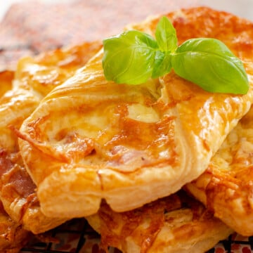 Flawless cheese and bacon turnovers with fresh basil on top