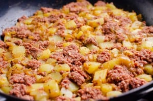 Cored beef and potatoes cooking in a cast iron pan