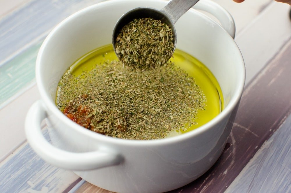 Dried mixed herbs being added to the olive oil mixture