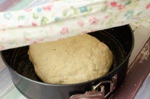 placing the bread dough in the oiled bread tin and covering it with a damp cloth to proof