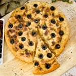 Olive Focaccia Bread on a wooden chopping board served with black olives and sun dried tomatoes on the side