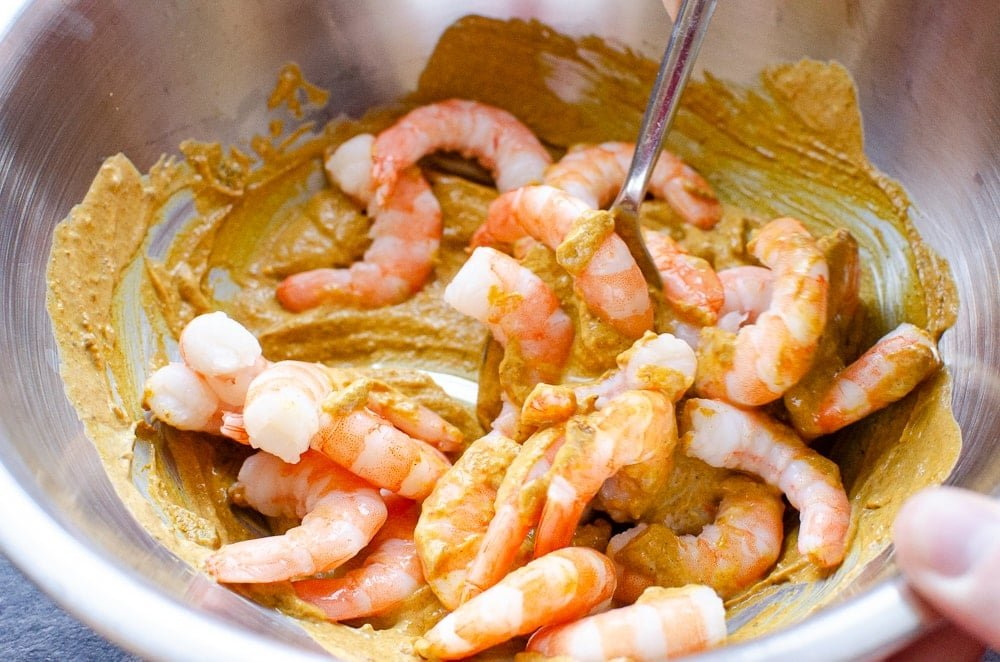Cooked King Prawns being mixed into spicy yoghurt sauce