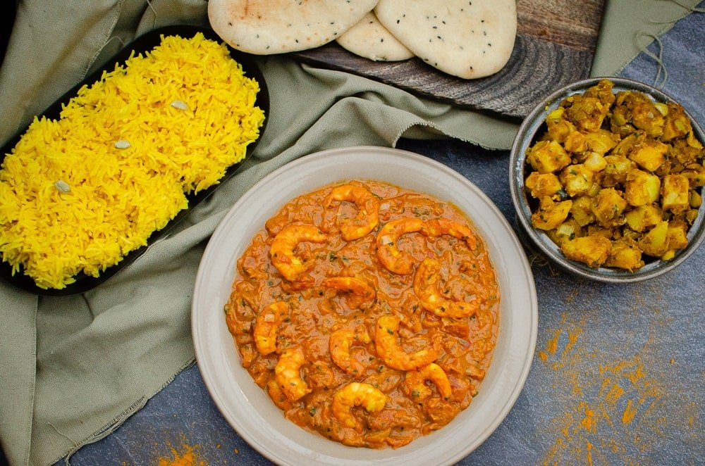 King Prawn Masala Curry served in grey bowl, with Bombay Potatoes, Naan Bread and Pilau Rice