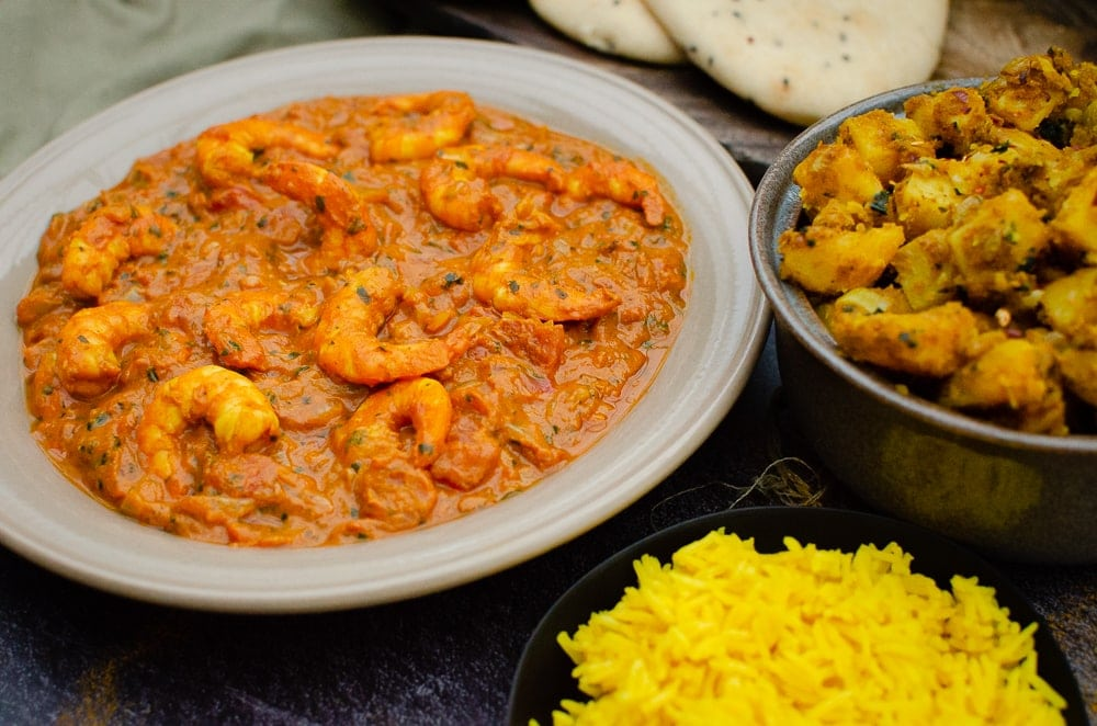 King Prawn Masala Curry served in grey bowl, with Bombay Potatoes and Pilau Rice