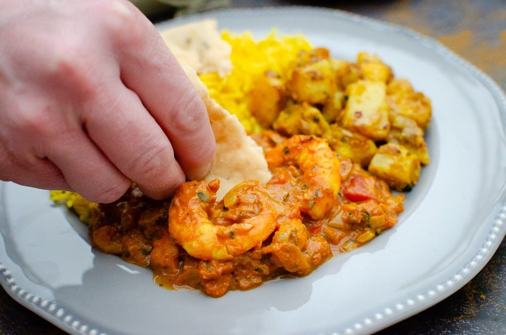 Dipping Naan Bread into King Prawn Masala Curry