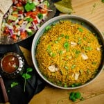 Pressure cooker Chicken Biryani served in a green bowl with chopped coriander on top, salad and mango chutney served on the side