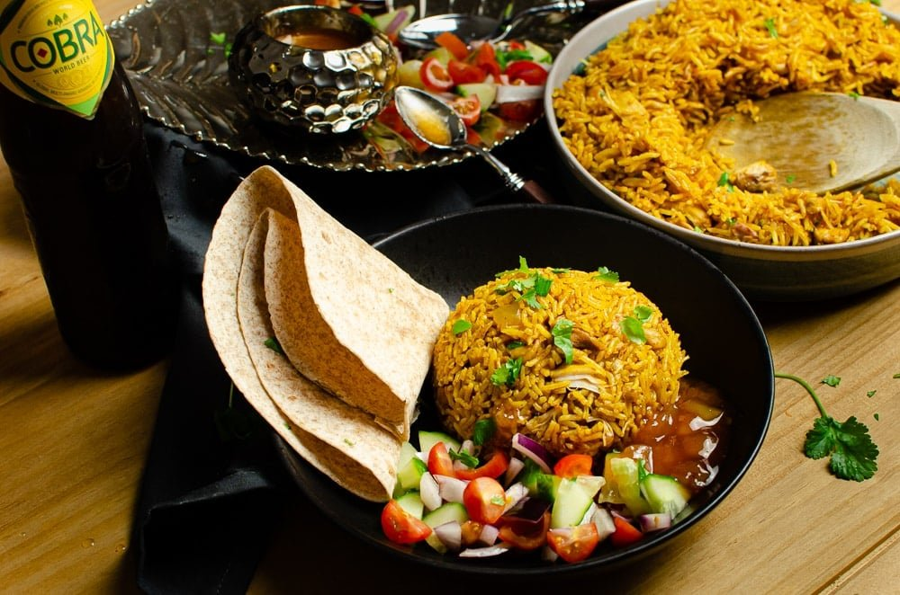 Pressure cooker Chicken Biryani served in a green bowl with chopped coriander on top, salad, mango chutney,Chapati and a bottle of cobra beer served on the side