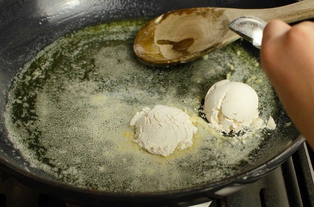 Melted butter and flour being stirred in a cast iron pan