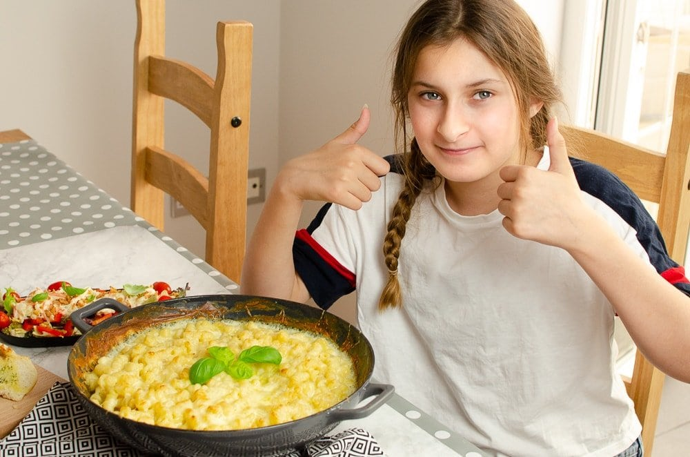 child with her thumbs up happy with her Easy cheesy past bake