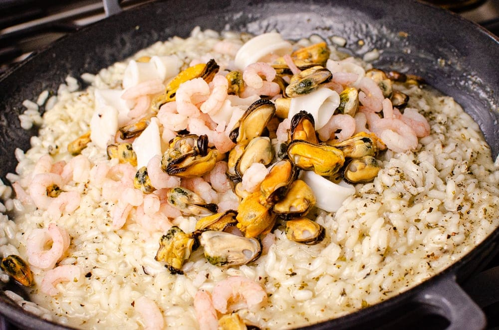 Mixed seafood mix being added to our risotto in a cast iron pan