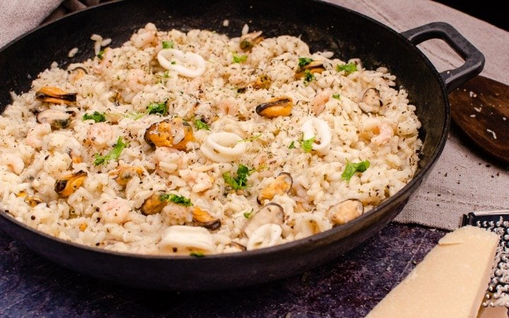 Mixed seafood risotto in a cast iron pan with Parmesan cheese on the side