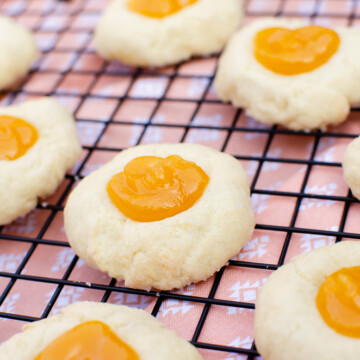 Passion Fruit Thumbprint Cookies on a black cooling rack