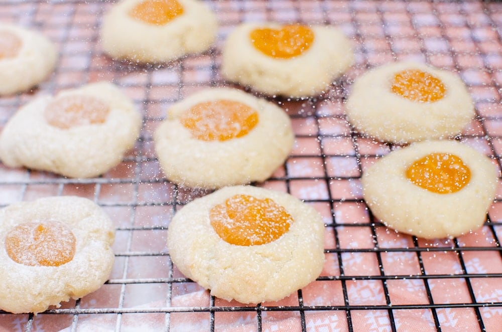 Sprinkling icing sugar over our Passion Fruit Thumbprint Cookies