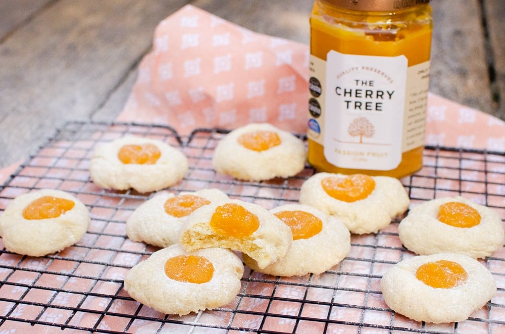 Passion Fruit Thumbprint Cookies on a black cooling rack with ajar of The Cherry Tree Passion fruit curd on the side