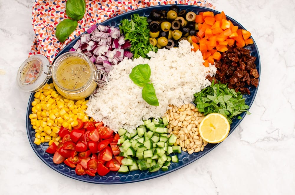 Sweetcorn,pine nuts chopped tomatoes,cucumber, basil, sun dried tomatoes, orange pepper, black and green olives,coriander, red onion,pot of Italian salad dressing and long grain rice in the middle of a large blue platter plate
