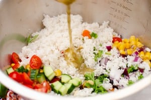 Italian style rice salad being mixed all together in a large silver bowl