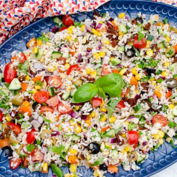 Italian Style Rice Salad on a large blue platter plate with lemon and basil on the side